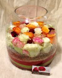 of multi colored roses in vase with decorative colored sand layers