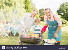 multi generation men grilling meat and corn at barbecue in