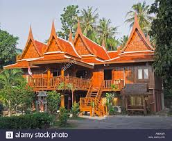carved wood traditional thai house and small spirit house in front