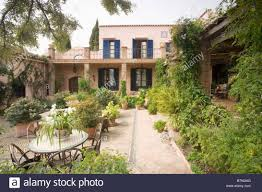 table and chairs on patio in spanish courtyard garden with stock