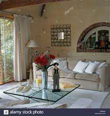 modern wood and glass coffee table wooden figure and vase of red roses on glass coffee table in