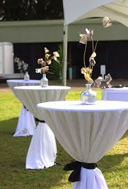 cocktail tables with white linen tablecloths and black sashes we