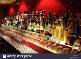 alcoholic drinks bottles row of alcoholic drink bottles on a pub bar with glasses uk stock