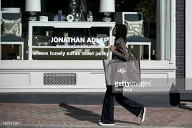 ugg sales figures carries a deckers outdoor corp ugg brand shopping bag past a picture id163511091 s 594x594