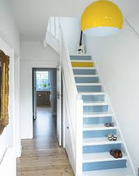 white hallway with painted stairs yellow lamp and one yellow step