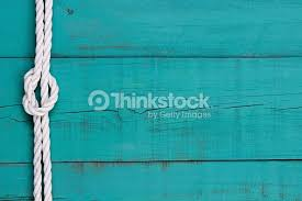 white rope with knot border on blue wood background stock photo
