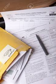 unpaid bills in a yellow envelope on a stack of tax forms for