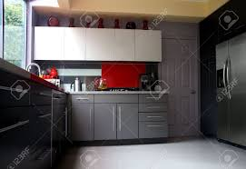 a modern kitchen with gray cabinets and glass backsplash stock a modern kitchen with gray cabinets and glass backsplash stock photo 3829840