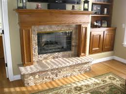 brown wooden fireplace mantel with cream stone surround and cream