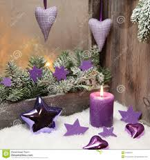 christmas decoration in violet or purple with wood and a candle