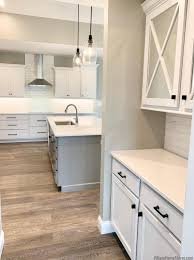 white kitchen cabinets with vinyl plank flooring white and gray kitchen with cambria delgatie home