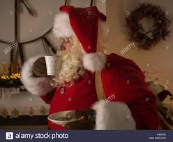 santa claus drinking milk near fireplace at home stock photo