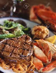 surf and turf grilled steak and crab legs stock photo picture