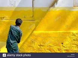 A Painter Paints The Wall Of An Old Building With Bright Yellow