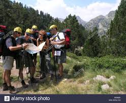 Catalonia Spain Map by Group Of Mountain Hikers Make Trekking And Reading Map In Stock