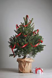 christmas tree with white lights and red bows christmas gift in a white box with a red bow on the floor next