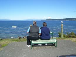woman and man sitting on a bench looking at the beach under blue