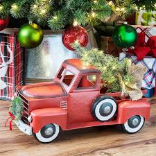 truck and station wagon with lit tree and wreath for