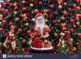 santa claus figure with a decorated christmas tree at back sao