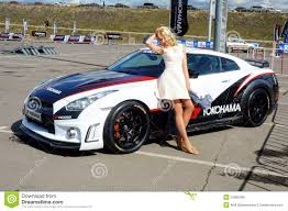 nissan sports car blue young beautiful woman posing next to the nissan gtr editorial