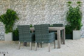 champagne weathered teak table with four grey wicker chairs cieux