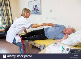 Home Nurse by Elderly Care In A Nursing Home Nurse Helps An Elderly Man Getting