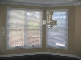 decorating white window with white faux wood blinds on beige wall