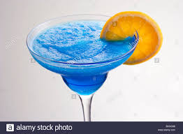 blue hawaiian cocktail frozen blue hawaiian mixed drink with orange slice garnish on grey