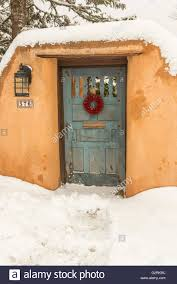 an aged wooden door with a red chili wreath on an adobe style home