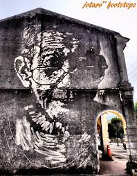 footsteps jotaro s travels art gallery balik pulau street art it depicts an old wrinkled silversmith and was carried out in an interesting way with a water jet blasting away a dark mossy wall to expose the original