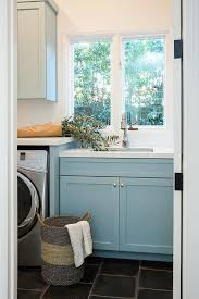 blue laundry room cabinets with oval brass knobs and slate floor