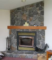 grey stone fireplace with brown wooden mantel shelf and black