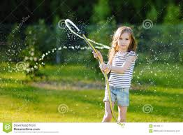 adorable little playing with a garden hose stock image