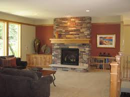 grey stone fireplace with brown wooden mantel shelf and square