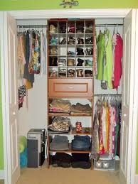white stained wooden closet organizer with shelf and clothes