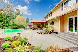 concrete floor backyard with swimming pool covered patio area