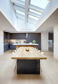 black island wide kitchen skylights white cabinets chairs pendant