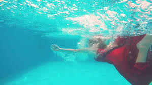 young blonde in long red dress jumps into the swimming pool