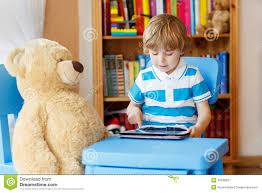 dans sa chambre peu de garçon d enfant jouant avec la tablette dans sa chambre à la