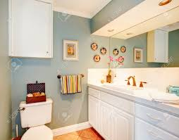cozy light blue bathroom with tile floor and white wood storage