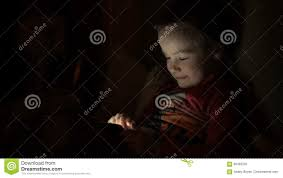 young child playing game on mobile phone in dark room stock