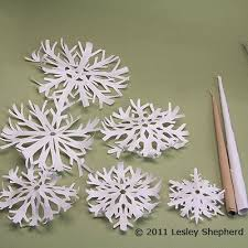 make simple winter trees from cut paper snowflakes