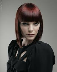 trendy bob hairstyle with a red hue and over the brows bangs