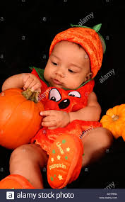 halloween black background pumpkin baby boy dressed as a halloween pumpkin on a black background