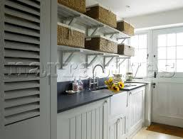 Kitchen Sink Shelves - storage baskets on open shelving above kitchen sink with cut