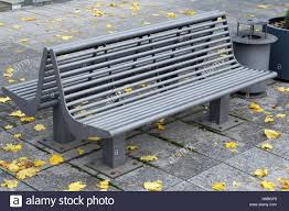 modern metal bench and recycle bin in the autumn city park stock