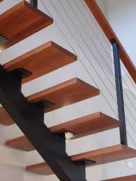 open stair with timber treads and steel structure beneath glass