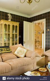 cream velour sofa in front of glass fronted cupboard in country