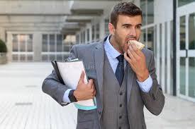 Meme Temps - homme d affaires marchant et mangeant en m礫me temps image stock