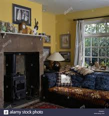 kelim rug on blue sofa beside fireplace with a small wood burning